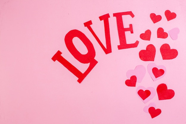 Vue de dessus coeur rouge autocollants amour en majuscules sur fond rose avec copie place