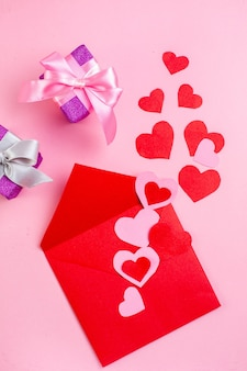 Vue de dessus coeur rouge autocollants enveloppe cadeaux sur fond rose