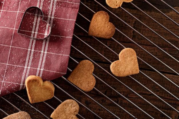 Vue de dessus des coeurs de biscuits sur une grille en métal avec une serviette en tissu rouge