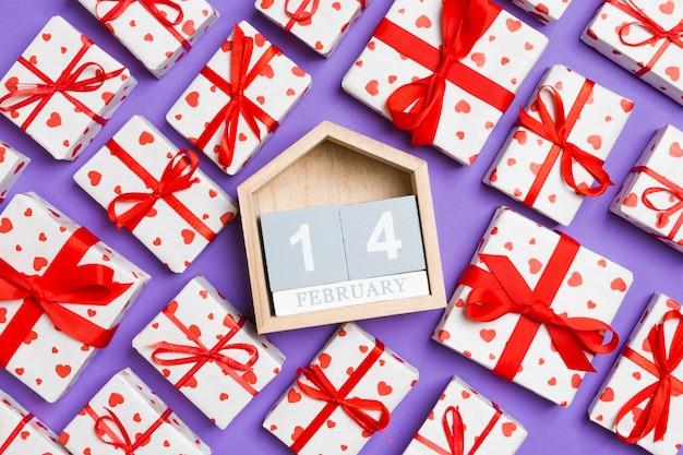 Vue de dessus des coffrets cadeaux blancs avec coeurs et calendrier en bois