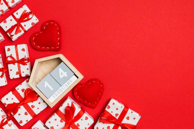 Vue de dessus des coffrets cadeaux, calendrier en bois et coeurs en textile rouge