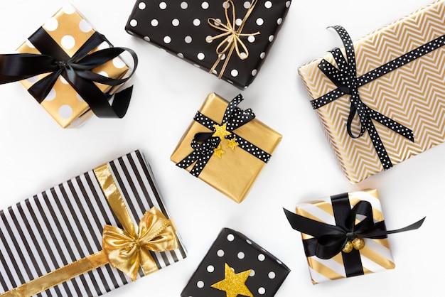 Vue de dessus des coffrets cadeaux dans divers dessins noirs, blancs et dorés. lay plat. un concept de noël, nouvel an, événement de fête d'anniversaire.