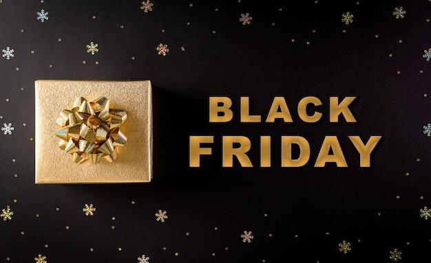 Vue de dessus des coffrets cadeaux de noël dorés sur fond noir avec texte black friday