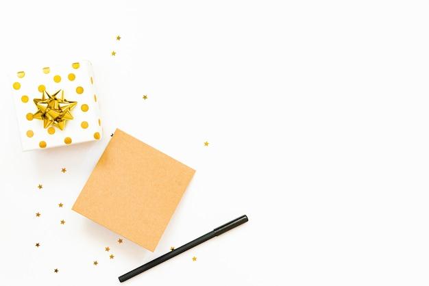 Vue de dessus des coffrets cadeaux en pointillés dorés et carte vide sur fond blanc. espace de copie, maquette.