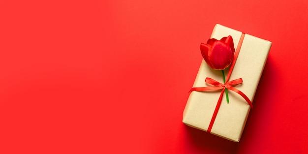 Vue de dessus des coffrets-cadeaux de printemps emballés avec des rubans rouges sur le dessus de table rouge.