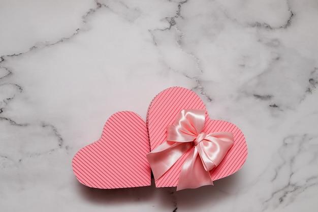 Vue de dessus coffrets cadeaux rose en forme de coeur sur fond de marbre avec espace copie