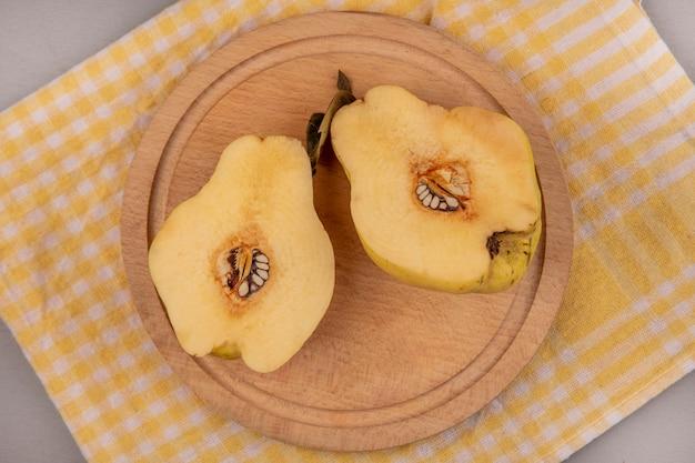 Vue de dessus de coings coupés en deux sur une planche de cuisine en bois sur un tissu à carreaux jaune