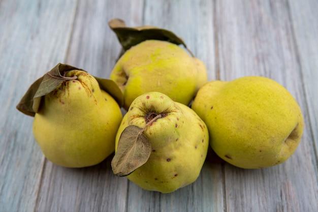 Vue de dessus des coings dorés frais avec des feuilles sur fond gris