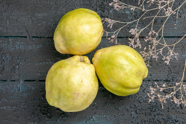 Vue de dessus des coings frais fruits moelleux et aigres sur un bureau bleu foncé plante fruitier aigre frais mûr