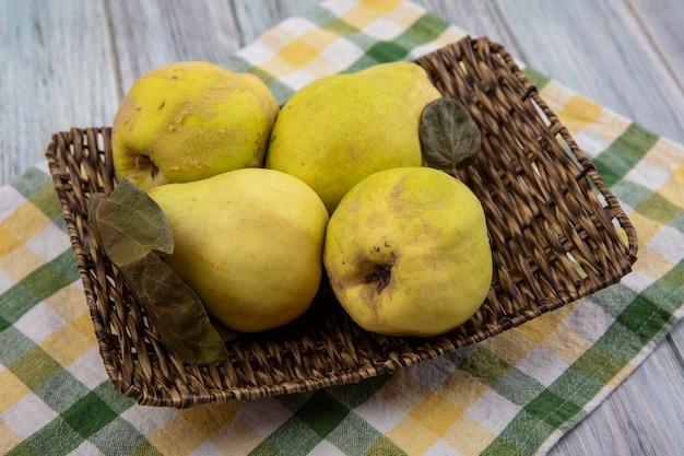 Vue de dessus de coings frais et sains avec des feuilles sur un plateau en osier sur un tissu vérifié sur fond gris