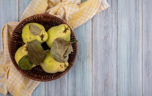 Vue de dessus de coings juteux frais avec des feuilles sur un seau sur un tissu à carreaux jaune sur fond gris avec copie espace