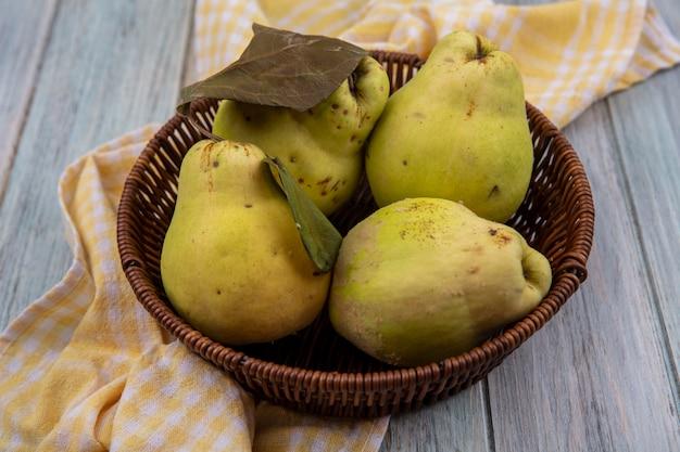 Vue de dessus de coings juteux frais avec des feuilles sur un seau sur un tissu à carreaux jaune sur fond gris