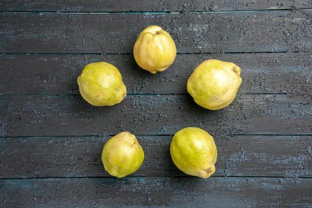 Vue de dessus coings mûrs frais fruits aigres bordés sur le bureau rustique bleu foncé plante fruitier mûr frais