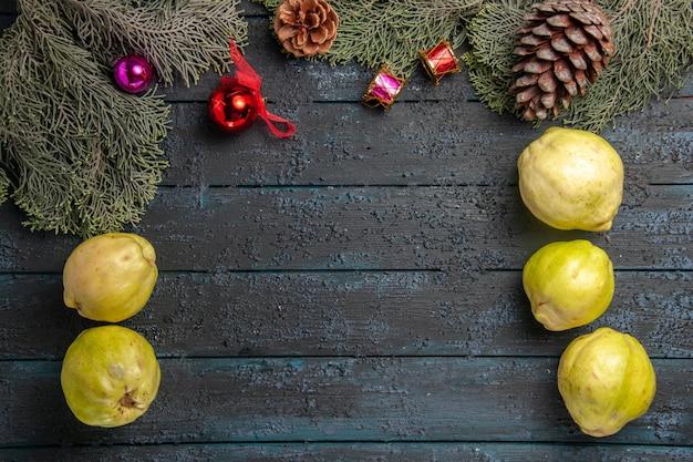 Vue de dessus coings mûrs fruits frais sur un bureau rustique bleu foncé beaucoup de plantes fraîches arbre fruitier mûr