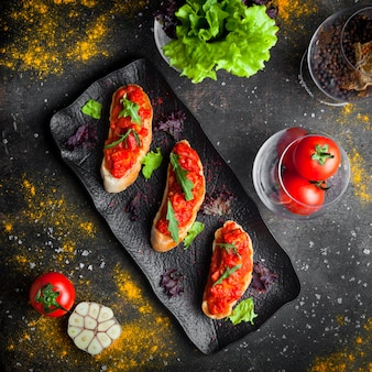 Vue de dessus collation avec et tranches de pain de dessus salade de tomates et roquette en plaque sombre