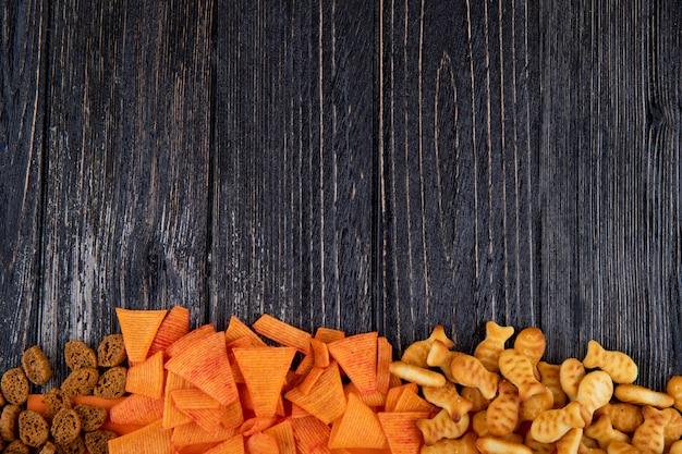 Vue de dessus collations chips de paprika mandrin dur et craquelins de poisson sur le fond avec copie espace sur fond noir