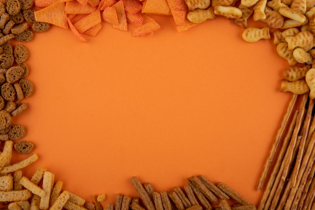 Vue de dessus des collations avec copie espace chips de paprika cracker sticks mandrin dur et mini brezel sur fond orange