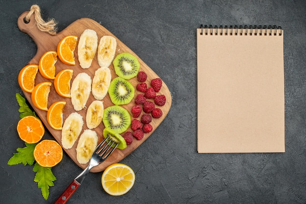 Vue de dessus de la collection de fruits frais hachés sur une planche à découper en bois et un cahier sur une surface sombre