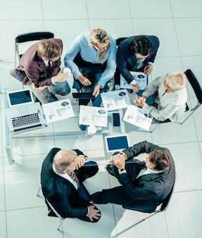 Vue de dessus. collègues de travail discutant des données financières lors d'une réunion de bureau. concept d'entreprise.