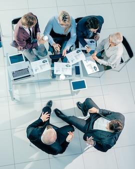 Vue de dessus des collègues de travail discutant des données financières lors d'une réunion de bureau