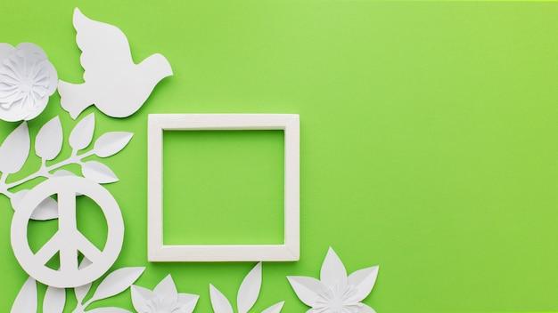 Vue de dessus de la colombe de papier avec cadre et signe de paix