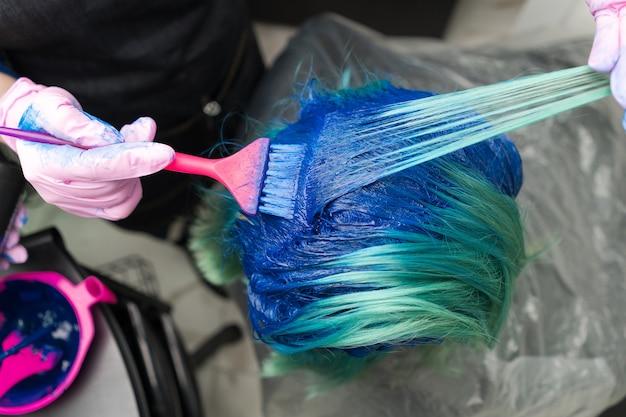 Vue de dessus de la coloration des cheveux dans un salon de beauté. coiffeur dans un gant de protection à l'aide d'un pinceau rose tout en appliquant de la peinture bleue au client avec une couleur de cheveux émeraude pendant le processus de teinture des cheveux en couleur unique