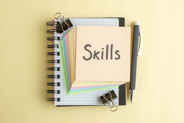 Vue de dessus compétences note écrite avec petit papier coloré notes sur fond clair bloc-notes de couleur école emploi bureau travail cahier
