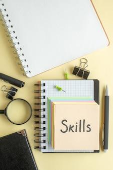 Vue de dessus compétences note écrite avec petit papier coloré notes sur fond clair bloc-notes emploi stylo école bureau affaires argent couleur travail cahier