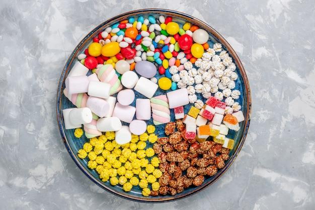 Vue de dessus composition de bonbons différents bonbons colorés avec guimauve sur bureau blanc sucre candy bonbon confiture sucrée