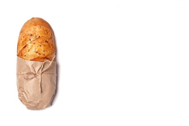 Vue de dessus de la composition ci-dessus, pain de blé frais fait maison, sans gluten, dans du papier kraft noué avec de la ficelle.