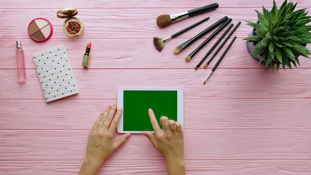 Vue de dessus de la composition créative avec des cosmétiques, des outils de maquillage, des accessoires et des mains de femme à l'aide de la tablette sur la surface de couleur. concept de beauté et de mode.