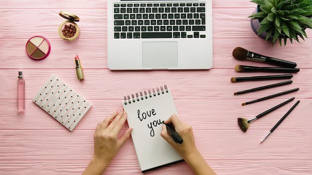 Vue de dessus de la composition décorée créative avec des cosmétiques, des outils de maquillage, des accessoires et des mains de femme écrivant sur le cahier de couleur. concept de beauté, mode et shopping.