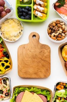 Vue de dessus composition de différents aliments avec planche de bois