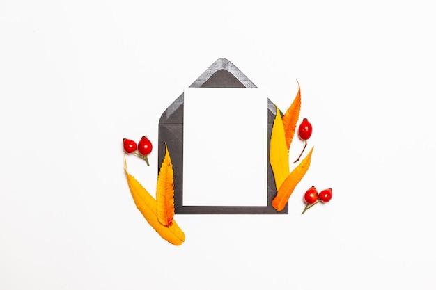 Vue de dessus composition de l'enveloppe de courrier vierge post maquette avec des feuilles jaunes d'automne
