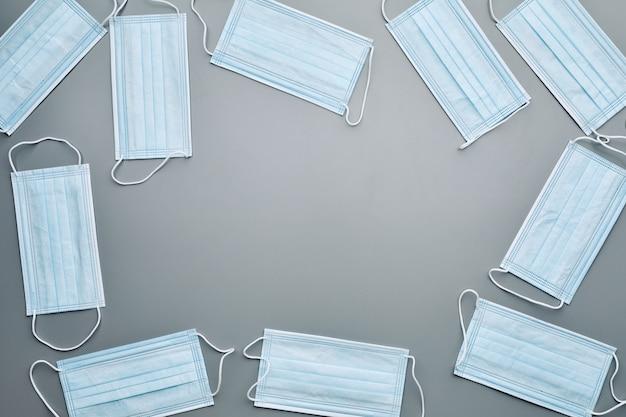 Vue de dessus composition de fond de masques médicaux encadrant un espace vide au centre sur fond gris,