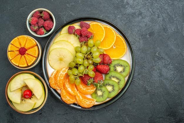 Vue de dessus composition de fruits délicieux fruits frais tranchés et moelleux sur fond sombre régime de santé frais fruits moelleux