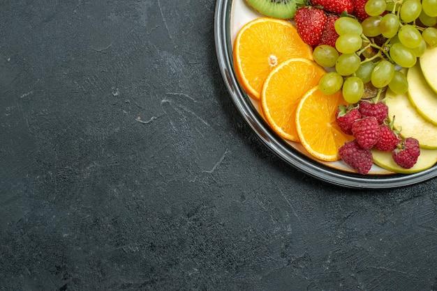 Vue de dessus composition de fruits délicieux fruits frais tranchés et moelleux sur fond sombre régime de santé frais et moelleux