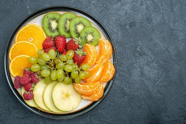 Vue de dessus composition de fruits délicieux fruits frais tranchés et moelleux sur fond sombre régime de santé mûr frais et moelleux