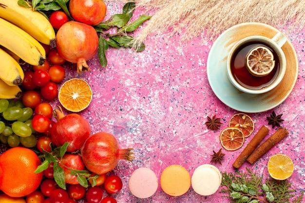 Vue de dessus de la composition de fruits frais avec des macarons français et du thé sur une surface rose clair