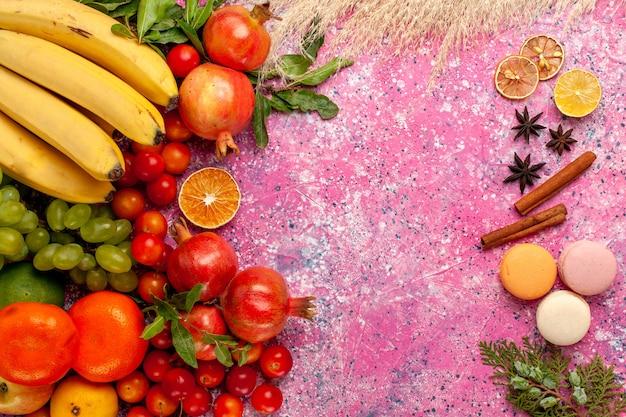 Vue de dessus de la composition de fruits frais avec des macarons français sur une surface rose clair