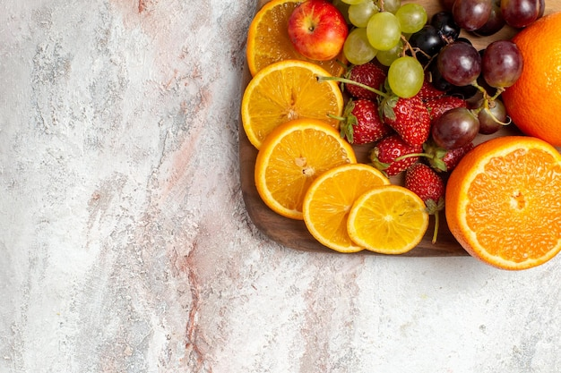Vue de dessus de la composition de fruits frais oranges raisins et fraises sur une surface blanc clair