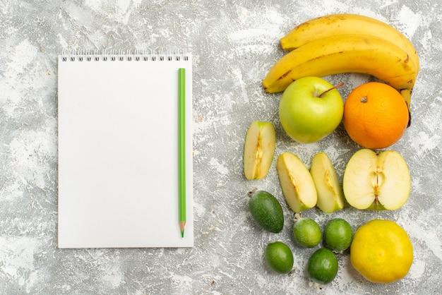 Vue de dessus de la composition de fruits frais pommes bananes feijoa et autres fruits sur fond blanc fruits frais mûrs couleur mûre vitamine
