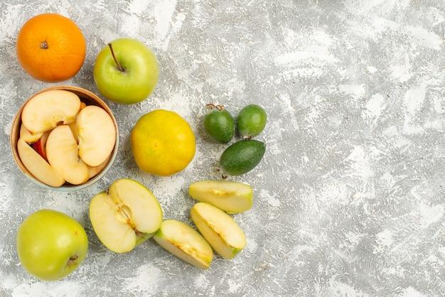 Vue de dessus composition de fruits frais pommes feijoa et autres fruits sur fond blanc fruits frais moelleux couleur mûre vitamine santé