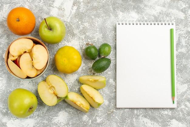 Vue de dessus de la composition de fruits frais pommes feijoa et autres fruits sur fond blanc fruits frais moelleux couleur mûre vitamine