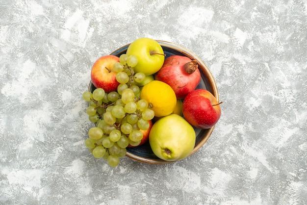 Vue de dessus composition de fruits frais pommes raisins et autres fruits sur le fond blanc fruits frais moelleux couleur mûre vitamine