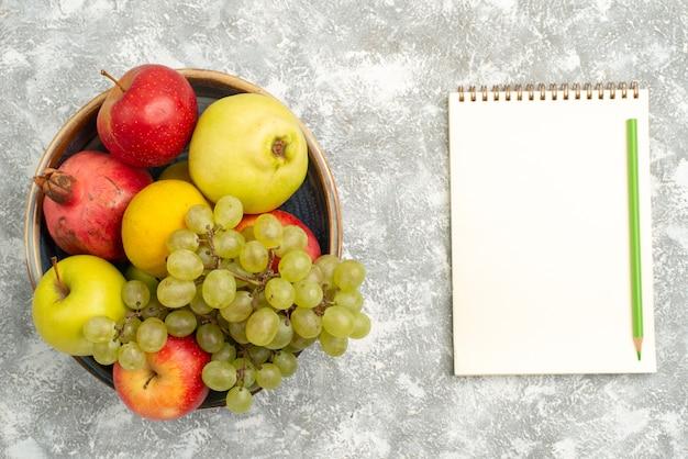 Vue de dessus composition de fruits frais pommes raisins et autres fruits sur fond blanc fruits frais moelleux couleur mûre vitamine