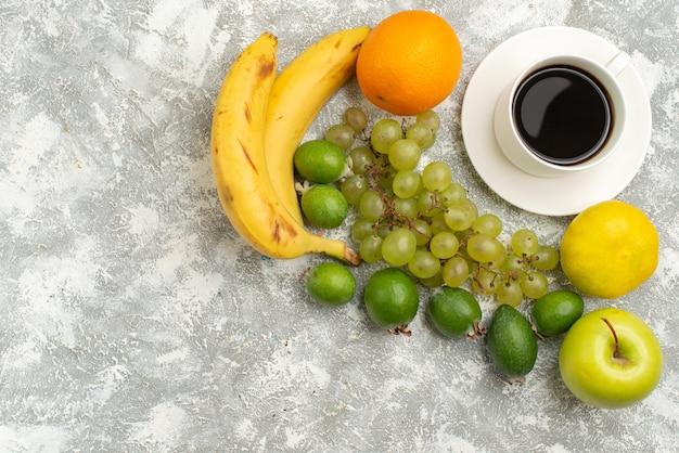 Vue de dessus de la composition de fruits frais pommes raisins et bananes avec du café sur fond blanc fruits frais moelleux couleur mûre vitamine