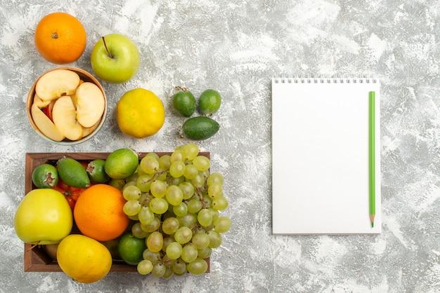 Vue de dessus composition de fruits frais raisins pommes feijoa et autres fruits sur fond blanc fruits frais moelleux couleur mûre vitamine santé