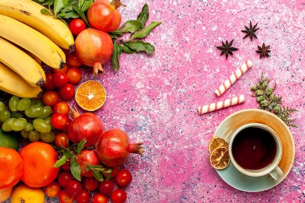 Vue de dessus de la composition de fruits frais avec une tasse de thé sur un bureau rose clair