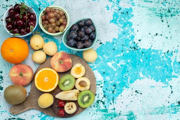 Vue de dessus de la composition de fruits en tranches et entières sur le biscuit exotique aux fruits fond bleu